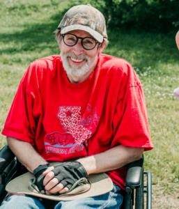 Een meneer in een rolstoel met een petje op