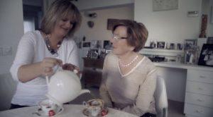 Mevrouw schenkt thee in voor een andere mevrouw