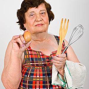 Vrouw met kookgerei en een ei in haar handen