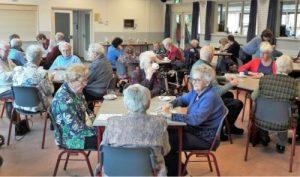 Een groep ouderen die samen in een ruimte zitten