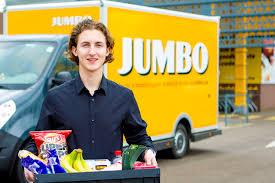 Een Jumbo werknemer die met een krat eten voor een jumbo busje staat.