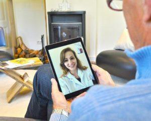 Man met een iPad waarmee hij aan het videobellen is