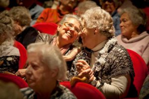 Twee ouderen die in het publiek naar een show kijken