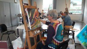 Een oudere vrouw die aan het schilderen is
