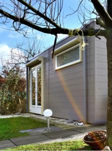 Foto van een huis met een spiegeling van een regenboog op de zijkant.