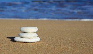 Foto van drie platte stenen op het strand op elkaar gestapeld.