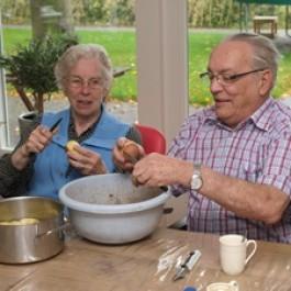 Oudere mensen die samen aardappelen aan het schillen zijn