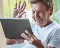 Mevrouw is aan het beeldbellen en zwaait naar de iPad