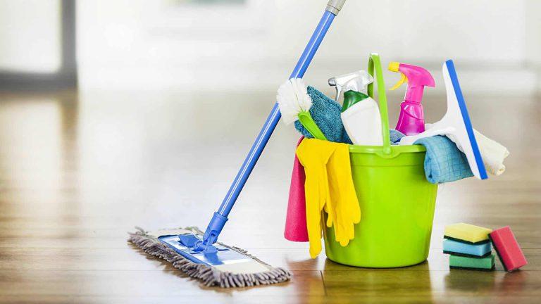 Een emmer met schoonmaakspullen en mop ernaast
