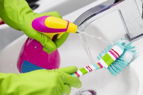 Iemand die met een afwasborstel een kraan en wasbak aan het schoonmaken is
