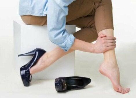Een vrouw die over haar been wrijft en haar schoen heeft uitgedaan