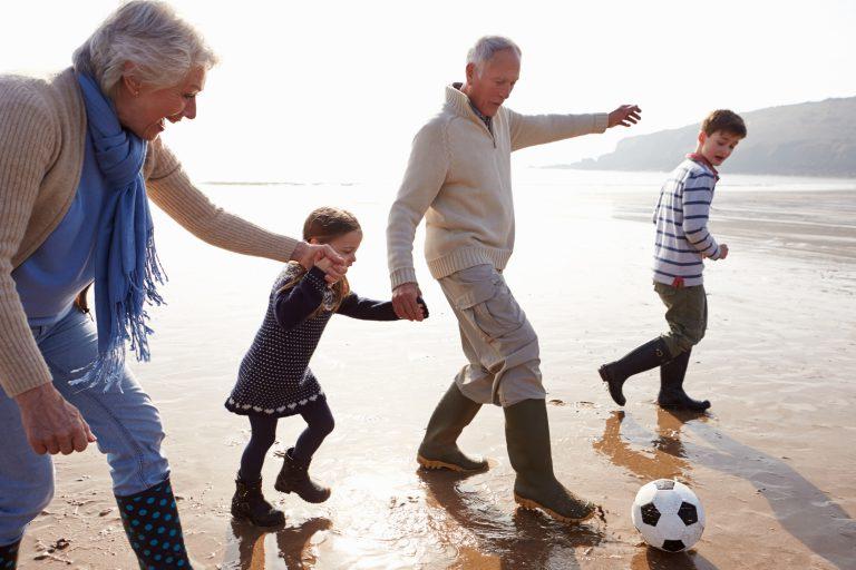 Kinderen die voetballen met opa en oma op het strand