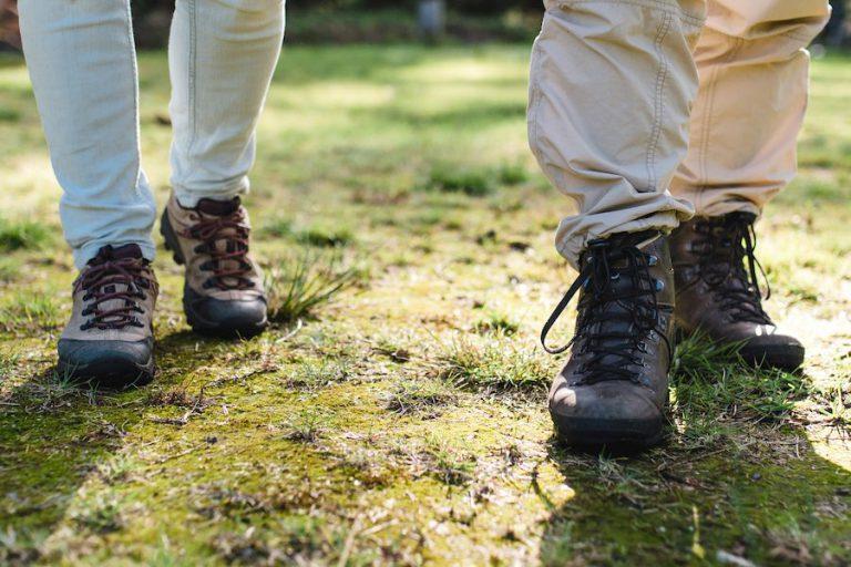 Mensen die wandelschoenen dragen en die door het gras aan het lopen zijn
