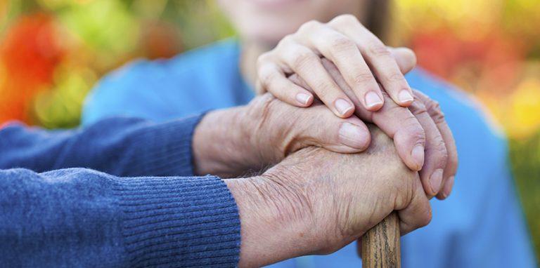 persoon die de handen vasthoud van een oudere man