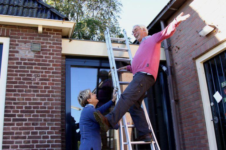 een meneer die met één been op een ladder staat