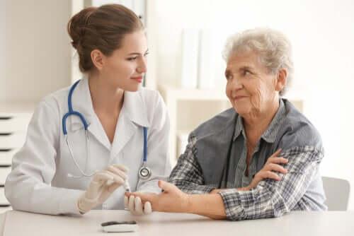 Een doktor die bloed prikt bij een oudere mevrouw