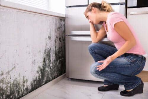 een mevrouw die naar schimmel kijkt in haar keuken