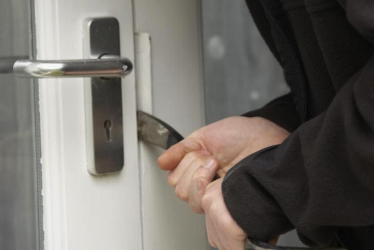 een afbeelding van een man die een koevoet tussen de deur heeft gezet en probeert in te breken