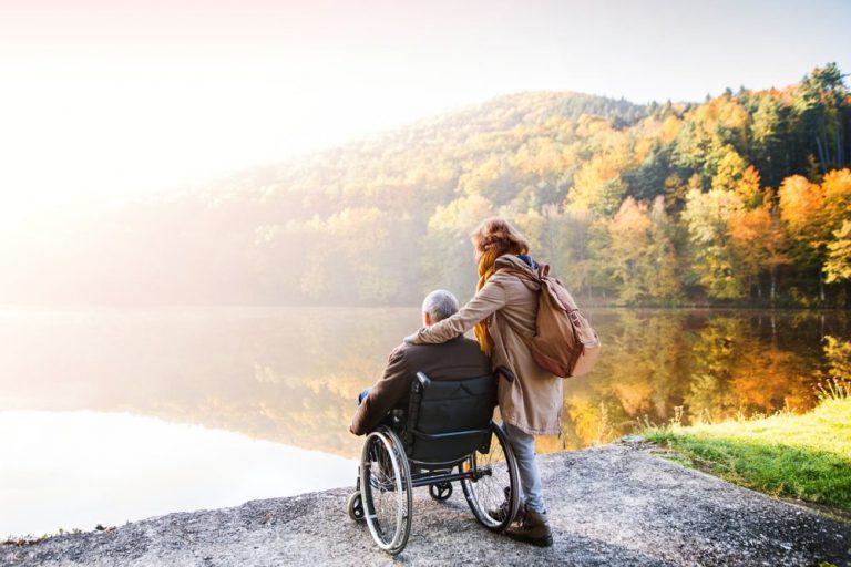 Vrouw staat met een man in een rolstoel aan de kant van het water