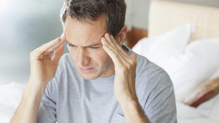 een meneer met zijn vingers tegen zijn hoofd en een pijnlijke uitdrukking