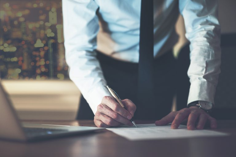een meneer die op een papier aan het schrijven is