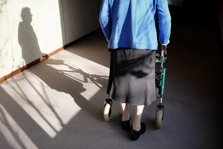 Een oudere vrouw met een rollator die onderweg is