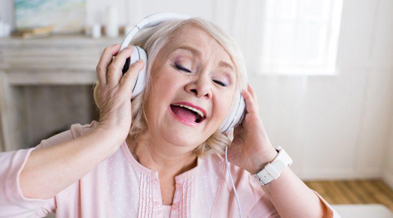 een mevrouw met een koptelefoon op die aan het meezingen is met de muziek