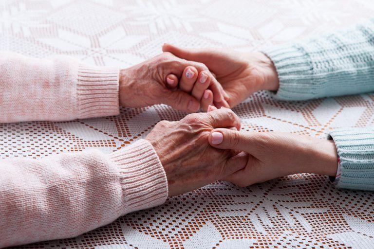 twee mensen die elkaars handen vasthouden