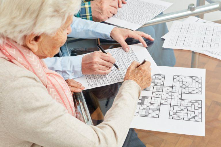 oudere mevrouw die sodoku aan het doen is en een meneer die een woordzoeker aan het doen is