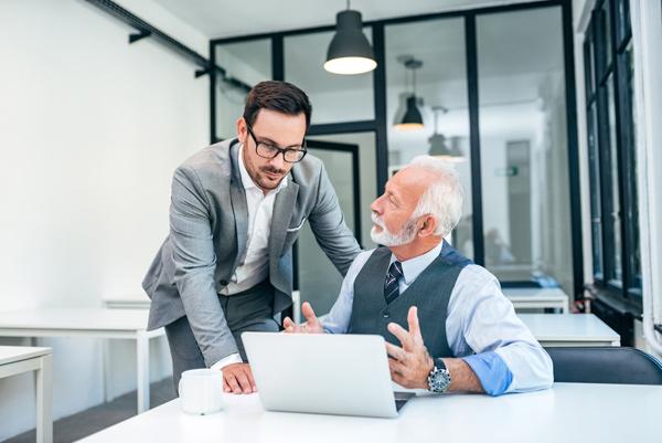 oudere man die achter een laptop ziet en met een meneer aan het praten is