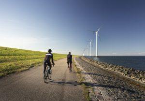 Foto van mannen die op racefietsen aan het fietsen zijn langs de zee
