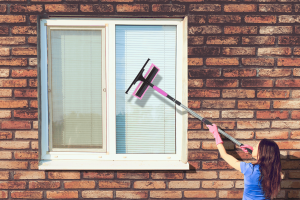 Afbeelding van een vrouw die de ramen aan het zemen is Klus Clean & Co